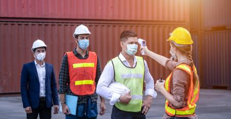factory workers with face masks having temperatures checked